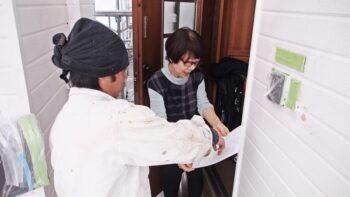 作業日報をお客様に渡している花まるリフォームの塗装職人