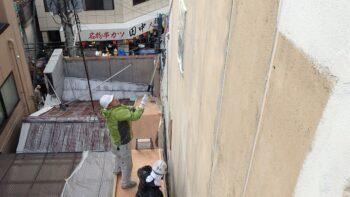 隣の屋根に乗って外壁塗装をする職人