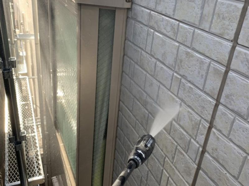 外壁の汚れを高圧洗浄で洗い流しています。